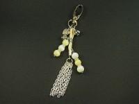 Bijou de sac avec des perles blanches et vanilles ainsi qu'un pompon